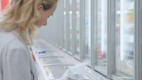 De vrouwelijke klant kiest de halffabrikaten die in de ijskast worden opgeslagen stock videobeelden