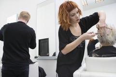 De Vrouwelijke Klant van kappergiving haircut to Stock Afbeelding