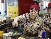 De vrouwelijke kok brengt hete braadpan met hulpmiddel Stock Foto's