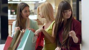 De vrouwelijke kopers in winkelcentrum met pakketten bekijken hun aankopen tijdens seizoengebonden verkoop stock video