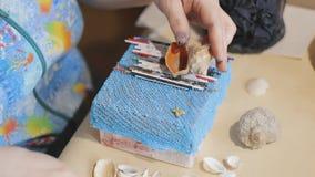 De vrouwelijke kunstenaar maakt een ontwerp op het hoogste dekkings blauwe document vakje met overzeese shells stock footage