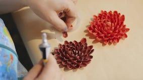 De vrouwelijke kunstenaar maakt een ontwerp van decoratieve bloemen met geschilderde nootshells stock video