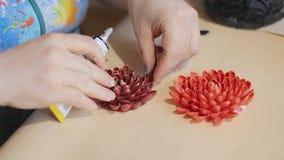De vrouwelijke kunstenaar maakt een ontwerp van decoratieve bloemen met geschilderde nootshells stock footage