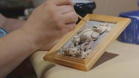 De vrouwelijke kunstenaar maakt het met de hand gemaakte schilderen v??r vernisproces schoon stock videobeelden