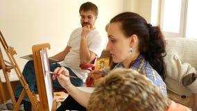 De vrouwelijke kunstenaar schildert beeldkunstwerk in kunststudio stock video