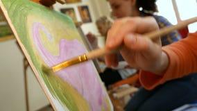 De vrouwelijke kunstenaar schildert beeldkunstwerk in kunststudio stock videobeelden