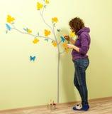 De vrouwelijke kunstenaar trekt boom, vlinders en vogels op de muur Stock Afbeelding