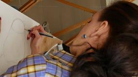 De vrouwelijke kunstenaar trekt een potloodschets in kunststudio stock videobeelden