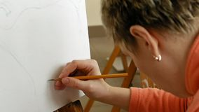 De vrouwelijke kunstenaar trekt een potloodschets in kunststudio stock video