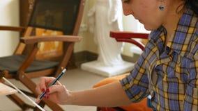 De vrouwelijke kunstenaar trekt een potloodschets in kunststudio stock footage