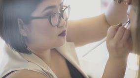 De vrouwelijke kunstenaar zet schaduw op ogen van zittingsdame in schoonheidssalon stock videobeelden