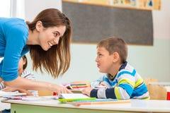 De vrouwelijke leraar toont de kinderen het boek, het lezen stock foto's