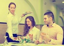 De vrouwelijke lijst van kelners dienende gasten Royalty-vrije Stock Foto