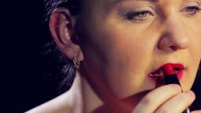 De vrouwelijke lippen van handverven met heldere rode lippenstift Close-up stock footage