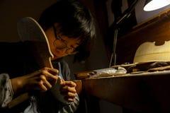 De vrouwelijke maker die van de vakmanviool aan een nieuwe viool werken stock foto