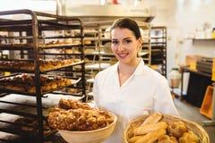 De vrouwelijke mand van de bakkersholding zoet voedsel stock foto's