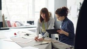 De vrouwelijke medewerkers van het naaien van studio werken met patronen en textiel, schetsen knipsel, spreken en gebruiken table stock video