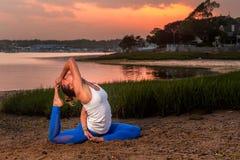 De vrouwelijke Meermin van Yoga Modeleka pada rajakapotasana stelt Strand Stock Fotografie