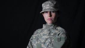 De vrouwelijke militair ziet de camera onder ogen stock footage