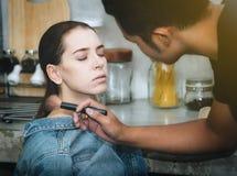 De vrouwelijke modellen kleuren hun gezichten met professionele make-up stock fotografie