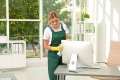De vrouwelijke monitor van de portier schoonmakende computer met vod royalty-vrije stock afbeeldingen