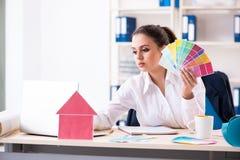 De vrouwelijke mooie ontwerper die in het bureau werken stock foto