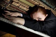 De vrouwelijke musicus gekleed in een mensen` s kostuum ligt op een pianotoetsenbord royalty-vrije stock fotografie