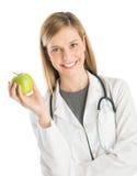 De vrouwelijke Oma Smith Apple van Artsenwith stethoscope holding Stock Afbeelding