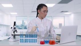 De vrouwelijke onderzoeker onderzoekt een vloeistof in een de gedragingen van de reageerbuisa vrouwelijk wetenschapper medisch on stock video