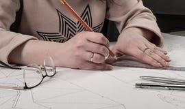 De vrouwelijke ontwerper maakt een werkende tekening Werkplaats van een stuk speelgoed ontwerper De tellers, de heerser, de pen e royalty-vrije stock fotografie
