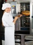 De vrouwelijke Oven van Chef-kokplacing pizza in royalty-vrije stock afbeelding