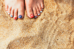 De vrouwelijke overzeese stijl pedicured voeten op het zand van de de zomerkust op zonnig DA Stock Afbeeldingen