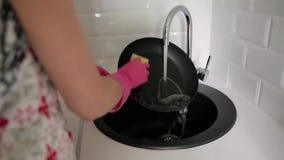 De vrouwelijke pan van de handwas onder lopend water stock footage