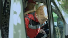 De vrouwelijke paramedicus krijgt in ziekenwagen, roepen de beroeps die naar noodsituatie gaan uit stock videobeelden