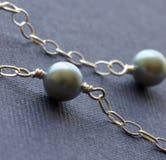 De vrouwelijke parels van de juwelenhalsband op kleurrijke backgro Stock Foto's