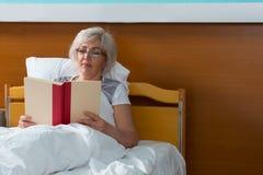 De vrouwelijke patiënt leest een boek, terwijl het liggen in het ziekenhuis is Stock Foto's
