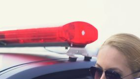 De vrouwelijke patrouilleambtenaar in glazen het goedkeuren roept en het krijgen in auto, handhaving stock video