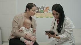 De vrouwelijke pediater arts toont iets stock videobeelden