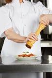 De vrouwelijke Peper van Chef-kokseasoning dish with Royalty-vrije Stock Afbeelding