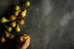 De vrouwelijke Peren van de Handenholding op Rustieke Donkere Achtergrond met Exemplaar S Royalty-vrije Stock Fotografie