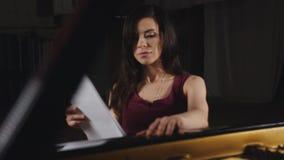 De vrouwelijke pianist zit door de piano en bespreekt muzieknota's stock videobeelden