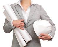 De vrouwelijke plannen van de architectenholding en een helm Stock Fotografie