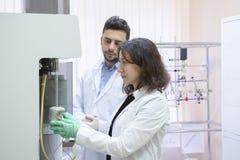 De vrouwelijke Reageerbuizen van Wetenschappelijk onderzoekeruses micropipette filling in een Groot Modern Laboratorium royalty-vrije stock foto's