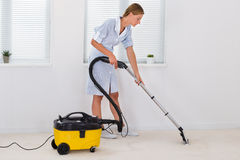 De vrouwelijke Reinigingsmachine van Meisjecleaning with vacuum Royalty-vrije Stock Foto