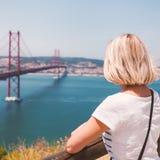 De vrouwelijke reiziger geniet van panorama's van Lissabon en de brug van 25 April Royalty-vrije Stock Fotografie