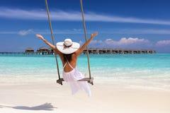 De vrouwelijke reiziger op een schommeling geniet van haar de zomervakantie royalty-vrije stock afbeeldingen