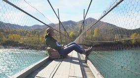 De vrouwelijke reiziger op de hangbrug door de bergrivier Mening van de rivier stock video