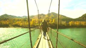 De vrouwelijke reiziger op de hangbrug door de bergrivier Mening van de rivier stock footage