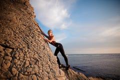 De vrouwelijke rotsklimmer beklimt op rotsachtige muur stock foto
