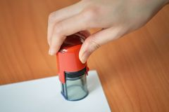 De vrouwelijke rubberzegels van de handgreep over lege document hoek bij bureaulijst, de spruit van het close-updetail Stock Fotografie